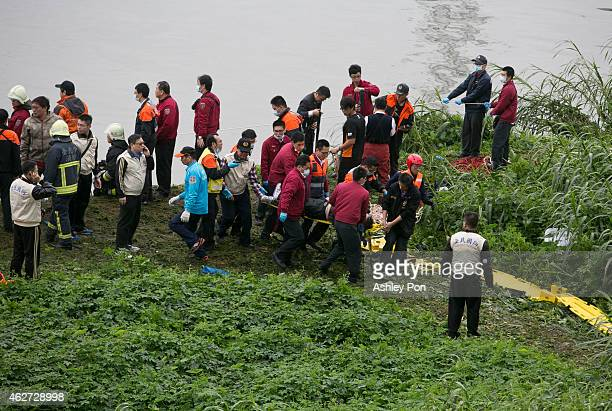 A rescue crew carries a passenger from a TransAsia Airways ATR 72600 turboprop airplane that crashed into the Keelung River shortly after takeoff...