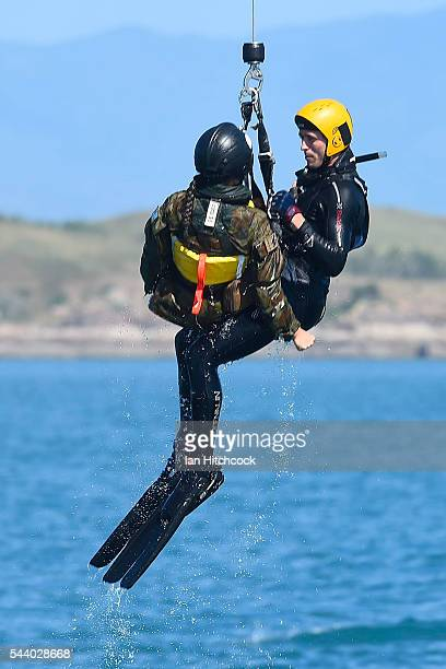 A rescue crewman is seen winching a simulated aircraft crash survivor up out of the ocean into the Royal Australian Air Force search and rescue...