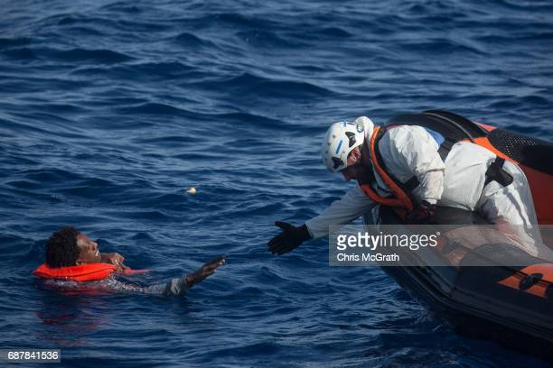 A rescue crewmember from the Migrant Offshore Aid Station 'Phoenix' vessel reaches out to pull a man into a rescue craft after a wooden boat bound...