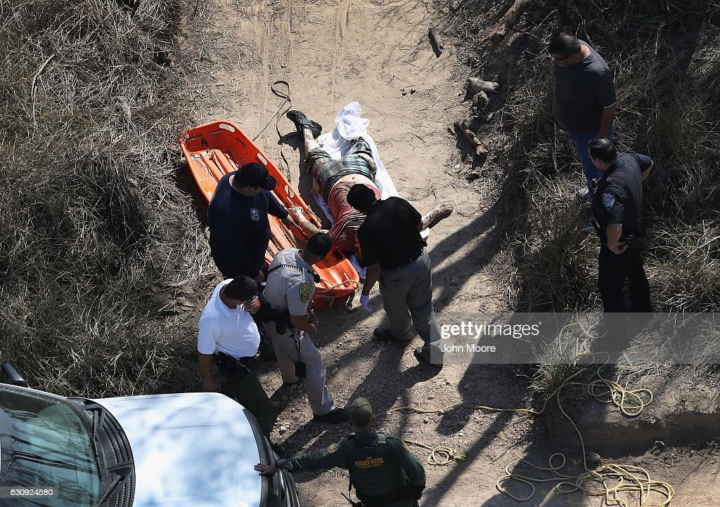 Rescue crews and U.S. Border Patrol agents remove a dead body from the banks of the Rio Grande on January 3, 2017 near Hidalgo, Texas. Thousands of immigrants are surging across the border ahead of the inauguration of President-elect Donald Trump, who has vowed to strengthen border security. Every year hundreds of immigrants die while making the perilous journey into the United States.