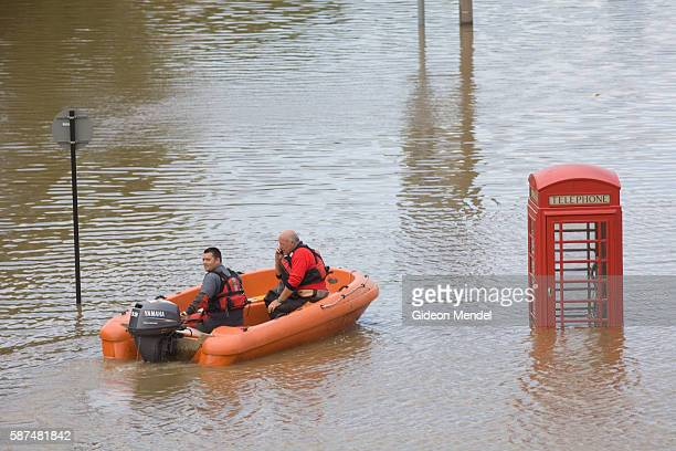 A rescue dingy passes a partly submerged traditional English phone box on one of the flooded streets of Catcliffe Village This was one of the...
