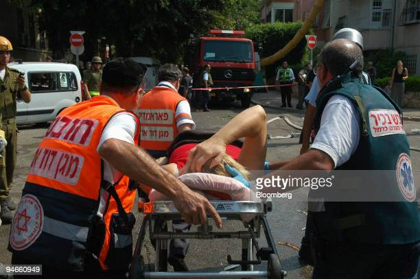 Rescue forces move a woman on a stretcher at a site where a katyusha rocket hit a building in Haifa Israel Monday July 17 2006 Israeli warplanes...
