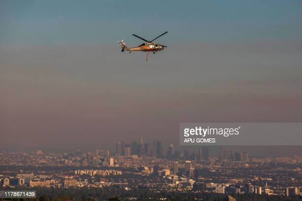 TOPSHOT A rescue helicopter flies over Brentwood while the Los Angeles skyline is seen behind smoke from the Getty Fire as seen from Brentwood...