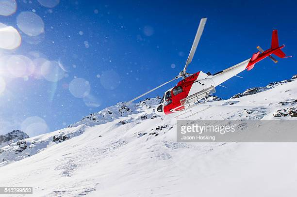 Rescue helicopter flying low over alpine terrain