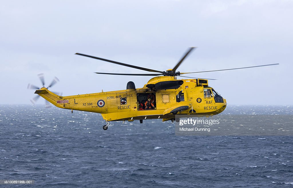 Rescue helicopter hovering above sea : Stockfoto