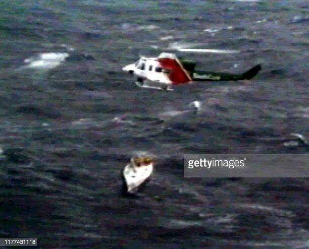 A rescue helicopter hovers above the stricken yacht Stand Aside to winch 12 crewmen to safety after gale force winds and huge waves pounded the boat...