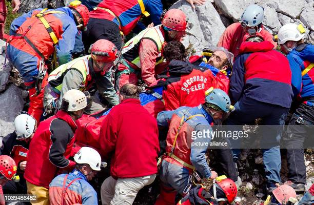 Rescue helpers carry injured cave explorer Johann Westhauser on a stretcher near the entrance to the Riesending cave at Untersberg mountain near...