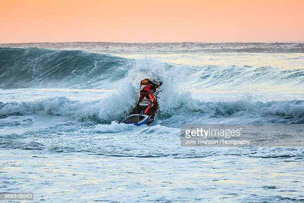 Rescue lifeguard jet ski heads out to check on surfers riding huge waves under a peaceful peach orange sky at Sunset Beach a famous tourist travel...