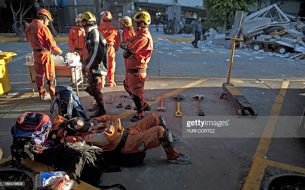 A rescue member takes a break after working looking for victims at the headquarters of state-owned Mexican oil giant Pemex in Mexico City on February 1, 2013, following a blast inside the building which leaves up to now 32 dead and 100 injured.