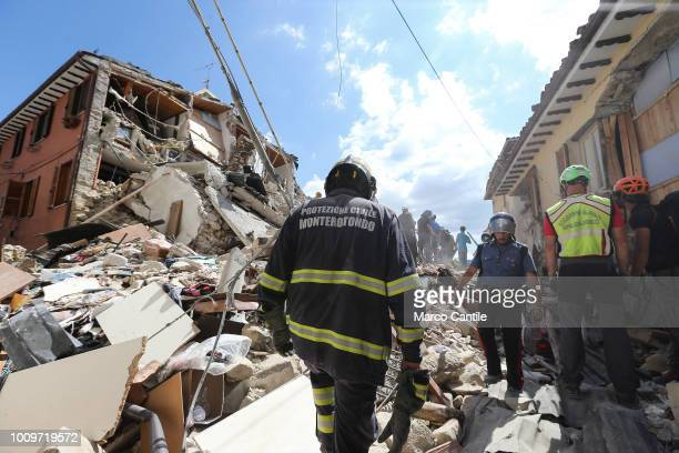A rescue men a fireman and a military man on the rubble of a house completely collapsed after the earthquake that hit the city of Amatrice in central...