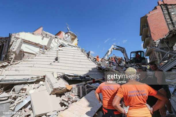 A rescue men and a excavator on the rubble of a two houses completely collapsed after the earthquake that hit the city of Amatrice in central Italy