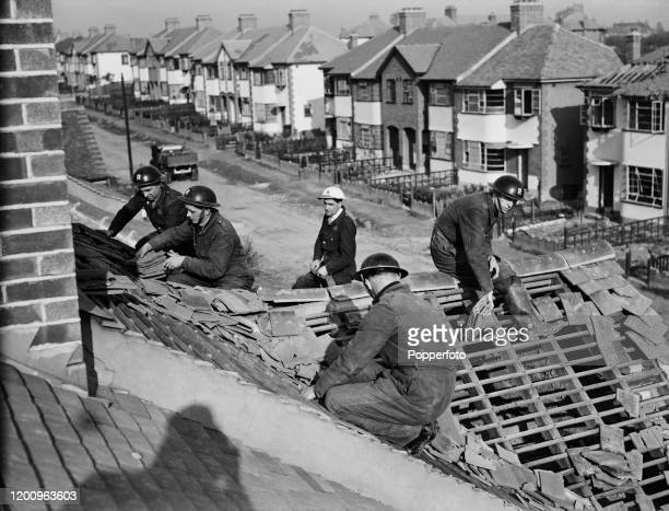 Rescue men salvage tiles from the roof of a residential house to be reused for repairs after a German Luftwaffe air raid on the town of Romford in...