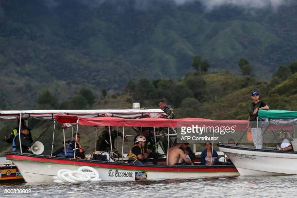 Rescue officials sit with survivors after the tourist boat Almirante sank in the Reservoir of Penol in Guatape municipality in Antioquia on June 25,...