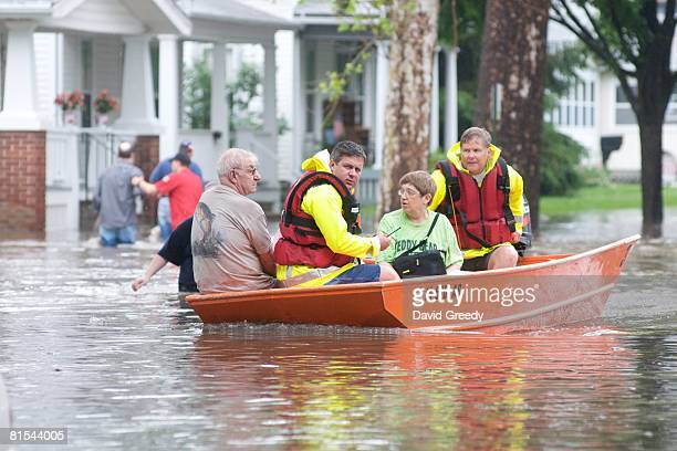 Rescue personal evacuate a family from their flooded home June 12, 2008 in Cedar Rapids, Iowa. Much of the city has been evacuated as the Cedar River...