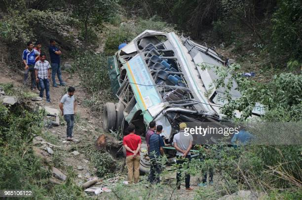 Rescue personnel and onlookers stand around a bus afer it fell off a mountain road into a deep gorge killing seven passengers near Gajerhi some 42...