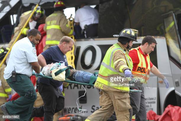 Rescue personnel carry a passenger from a charter bus that was hit by a CSX train at the Main Street crossing in Biloxi Miss on Tuesday March 7 2017