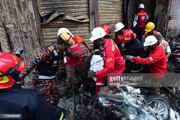 Rescue personnel carry the body of a victim after a fire broke out in Dhaka on February 21 2019 At least 69 people have died in a huge blaze that...