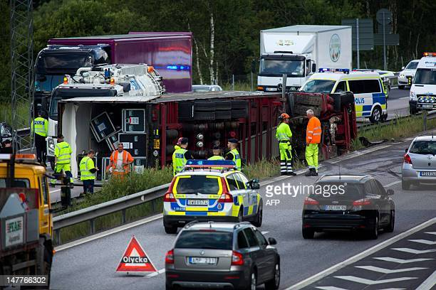 Rescue personnel clear the cargo from an overturned semi trailer on the motorway south of Goteborg Sweden on July 3 2012 The trailer carrying the...