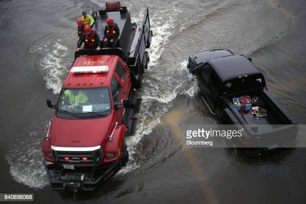 Rescue personnel drive past an abandoned pickup truck in floodwaters from Hurricane Harvey in Dickinson Texas US on Tuesday Aug 29 2017 Estimates for...