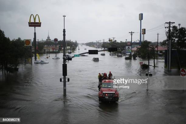 Rescue personnel drive through an intersection covered with floodwaters from Hurricane Harvey in Dickinson Texas US on Tuesday Aug 29 2017 Estimates...