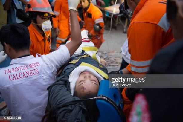 Rescue personnel evacuate earthquake survivor Ida a food vendor from the rubble of a collapsed restaurant in Palu Indonesia's Central Sulawesi on...