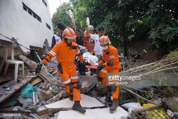 TOPSHOT Rescue personnel evacuate earthquake survivor Ida a food vendor from the rubble of a collapsed restaurant in Palu Indonesia's Central...