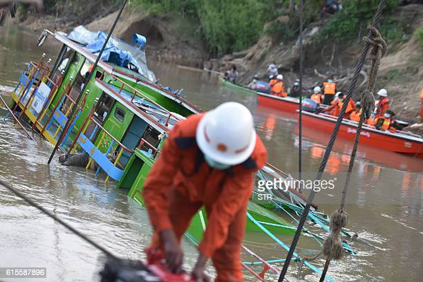 Rescue personnel from the Myanmar Fire Services Department refloat a ferry which sank in the Chindwin River in the Sagaing region on October 19 2016...
