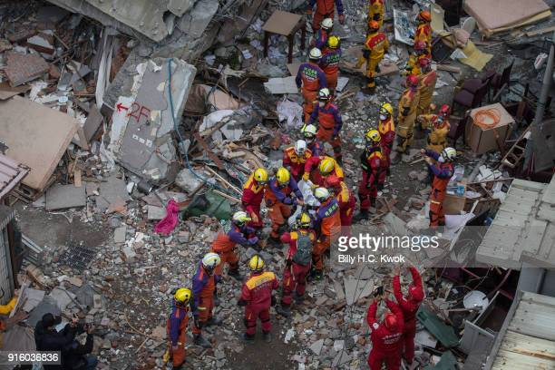Rescue personnel move the body of a victim from a collapsed buidling on February 9 2018 in Hualien Taiwan The 64 magnitude earthquake hit late...