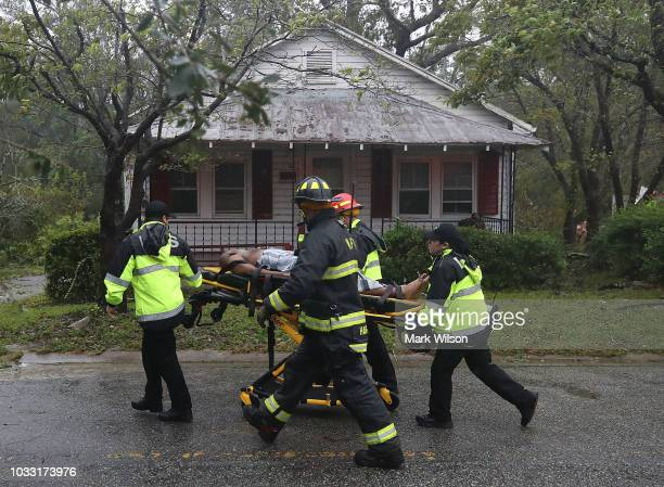 Rescue personnel remove a man from a home that a large tree fell on that had three people trapped after Hurricane Florence hit the area on September...