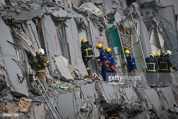 Rescue personnel search for survivors at the site of a collapsed building in the southern Taiwan on February 6 2016 in Tainan Taiwan A magnitude 64...