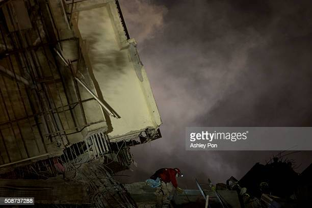 Rescue personnel search for survivors at the site of a collapsed building in the southern Taiwa on February 6 2016 in Tainan Taiwan A magnitude 64...