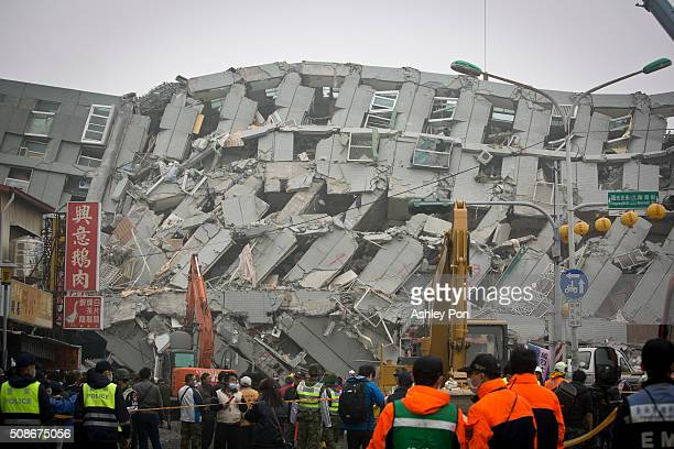 Rescue personnel search for survivors at the site of a collapsed building on February 6 2016 in Tainan Taiwan A magnitude 64 earthquake hit southern...