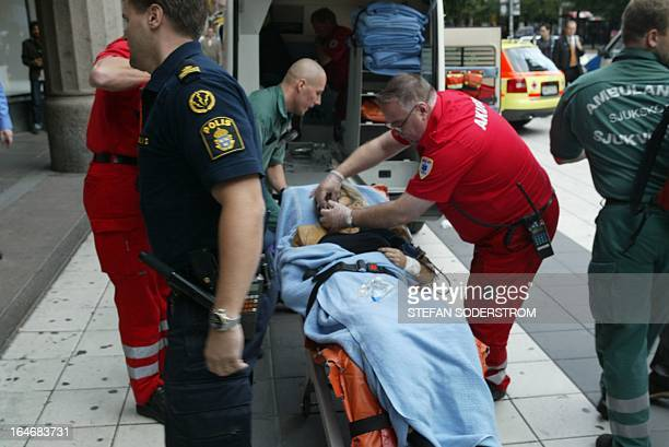 Rescue personnel take care 10 September 2003 of Swedish Foreign Minister Anna Lindh lying on a stretcher outside the NK department store in central...