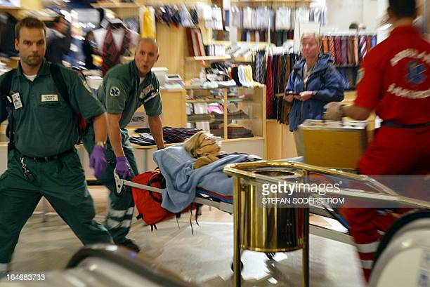 Rescue personnel take care 10 September 2003 of Swedish Foreign Minister Anna Lindh lying on a stretcher at the NK department store in central...