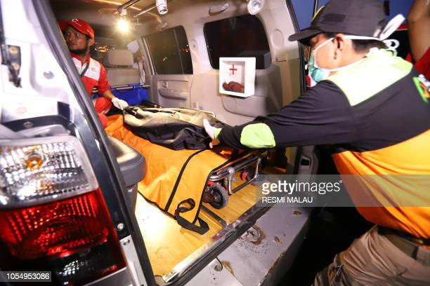 Rescue personnel transfer a bag containing human remains into an ambulance at port in Tanjung Priok North Jakarta on October 29 after being recovered...
