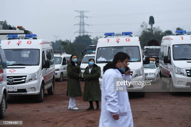 Rescue personnel wait beside parked ambulances outside the Diaoshuidong coal mine in southwestern China's Chongqing on December 5 after a carbon...