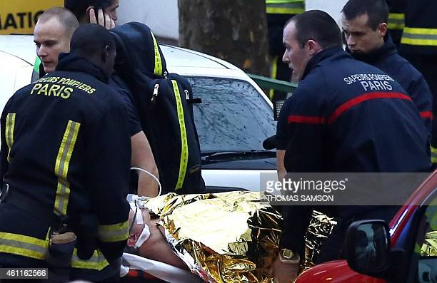 Rescue service workers and firefighters evacuate an injured person on a stretcher near the site of a shooting on the morning of January 8 2015 in...
