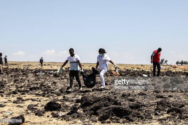 TOPSHOT Rescue team carry collected bodies in bags at the crash site of Ethiopia Airlines near Bishoftu a town some 60 kilometres southeast of Addis...