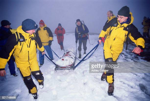 rescue team carrying body in snow - rescue worker stock pictures, royalty-free photos & images