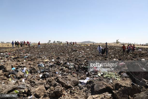 TOPSHOT Rescue team collect bodies in bags amid debris at the crash site of Ethiopia Airlines near Bishoftu a town some 60 kilometres southeast of...
