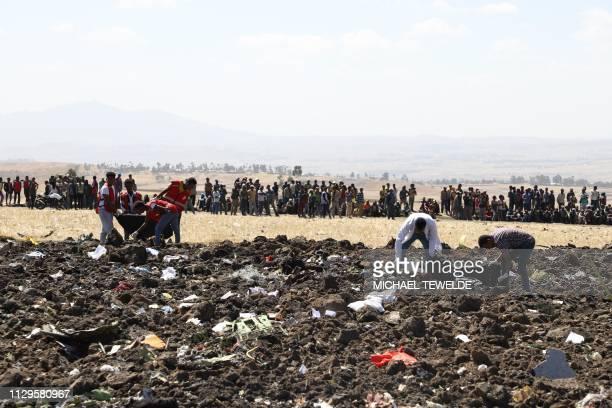Rescue team collect remains of bodies amid debris at the crash site of Ethiopia Airlines near Bishoftu a town some 60 kilometres southeast of Addis...