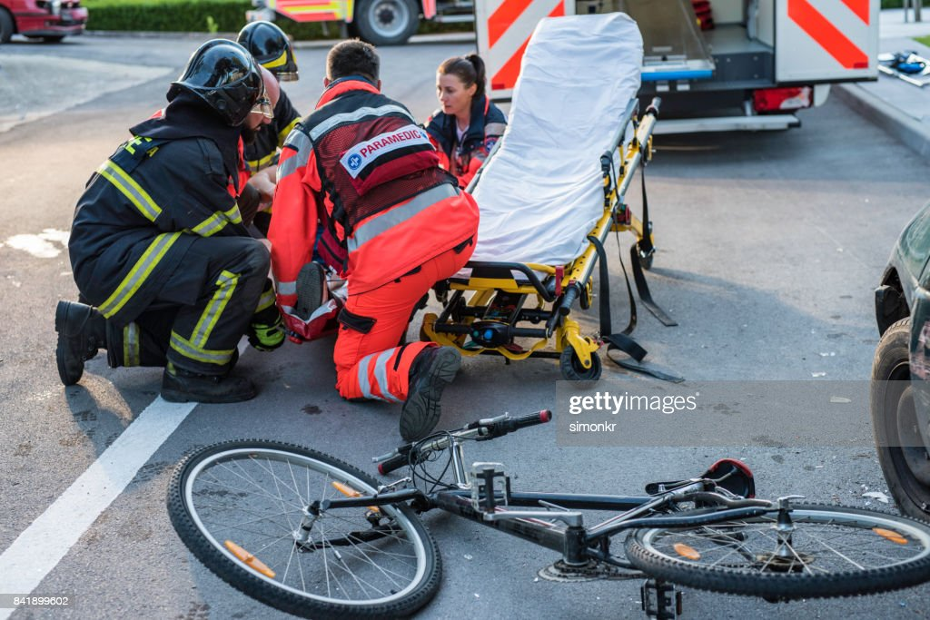 Rescue team helping cyclist : Stock Photo