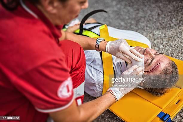 soccorso aiutando uomo ferito - croce rossa organizzazione foto e immagini stock