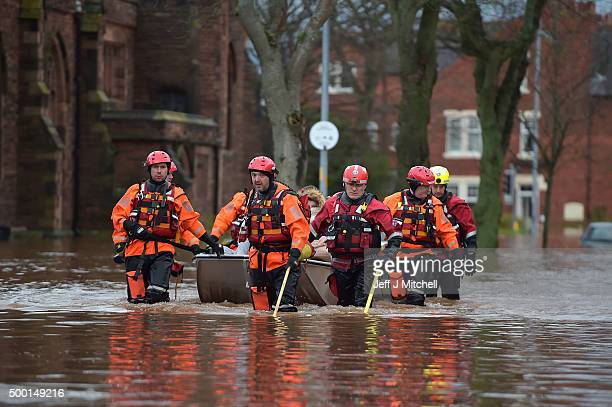 A rescue team helps to evacuate people from their homes during heavy flooding on December 6 2015 in Carlisle England Storm Desmond has brought severe...