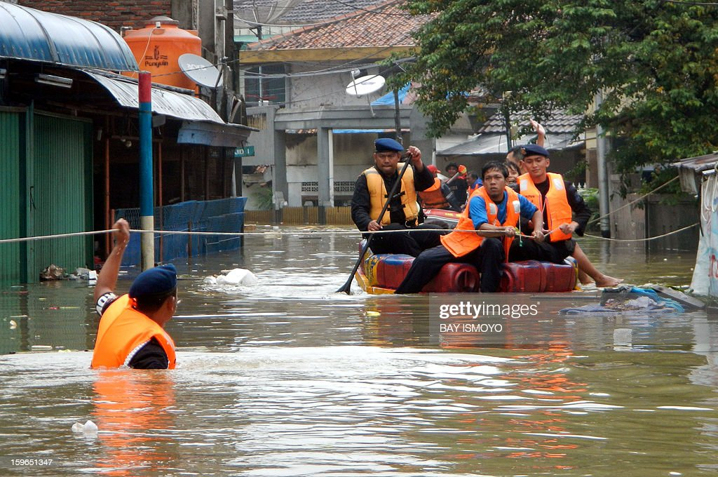 A rescue team looks for people stuck in their homes in a flooded area of Jakarta on January 18, 2013. Floods in Indonesia's capital Jakarta have left at least 11 people dead, authorities said on January 18 as murky brown waters submerged parts of the city's business district, causing chaos for a second day. AFP PHOTO / Bay ISMOYO