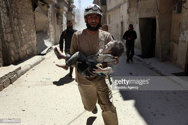 A rescue team member carries an injured child after Syrian forces airstrike over Aleppo's opposition controlled AlSahur district Syria on May 30 2016