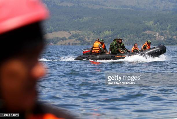 Rescue team members search for missing passengers on Lake Toba in the province of North Sumatra on June 22 after a ferry capsized on June 18...