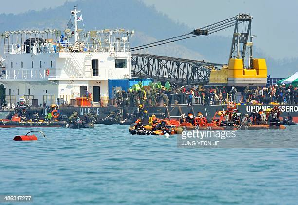 Rescue team personnel take part in recovery operations at the site of the sunken South Korean ferry 'Sewol' marked with buoys at sea off Jindo on...