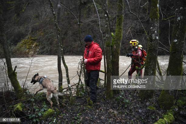 A rescue team searches with a dog on the banks of the Breda River for a volunteer firefighter who has been reported missing after having fallen into...