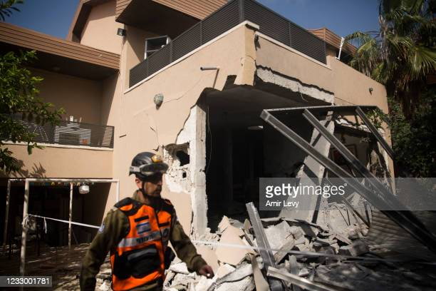Rescue team soldier work at the house where a rocket fired from the Gaza Strip hit Sigal's house on May 20, 2021 in Ashkelon, Israel. In a press...